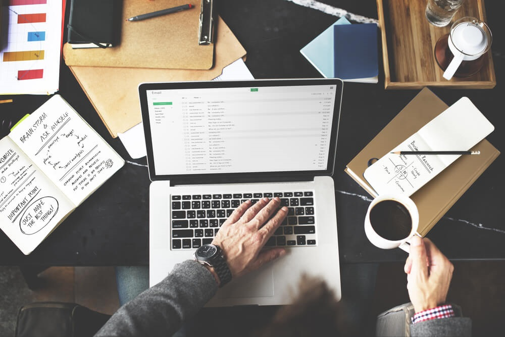 email marketing specialist with an open laptop and coffee mug